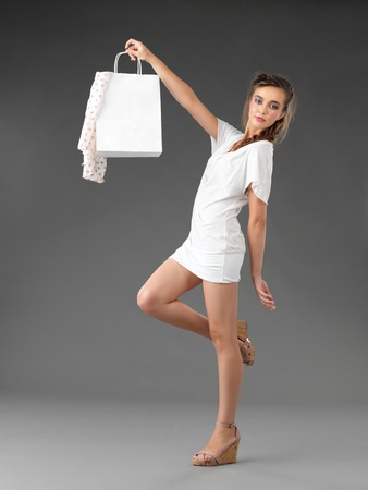 adjusting: fashionable young woman holding a shopping bag Stock Photo