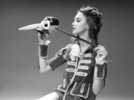damas antiguas: negro del estudio y el retrato de la moda blanco de la mujer joven en traje de época, posando con máscara veneciana Foto de archivo