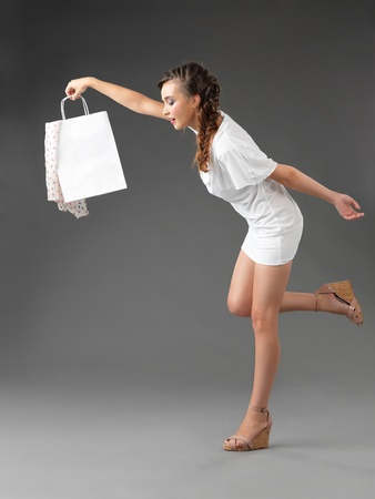 fashionable young woman holding a shopping bag, tumbling photo