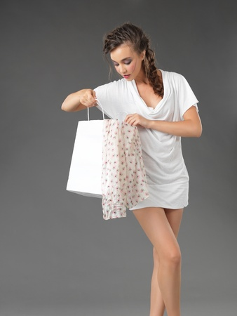 fashionable young woman looking inside a shopping bag photo