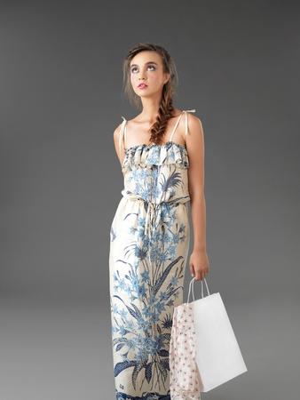 fashionable young woman walking, holding a shopping bag photo