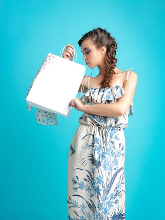 fashionable young woman standing, holding a shopping bag, on blue background, looking inside the bag photo