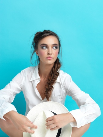 young woman sitting on blue background, with white hat and mans shirt, copy space photo