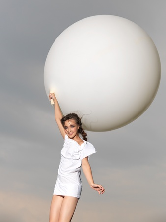 happy, young woman jumping with big, white balloon photo