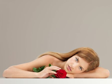 beauty portrait of young, blonde woman resting her head on her arm, holding a red rose photo