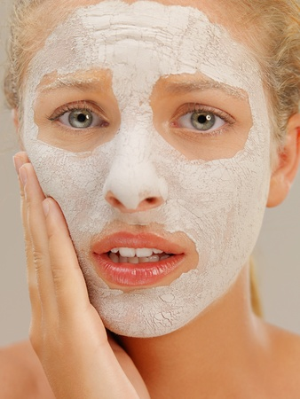 closeup beauty portrait of beautiful blonde woman with a facial mud mask on her skin, touching her face, with worried face expression photo
