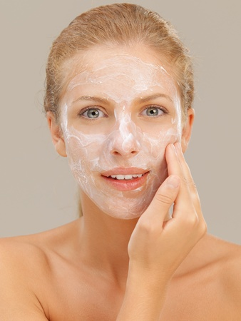 dry skin: closeup beauty portrait of beautiful blonde woman with a facial moisturizer mask on her skin, touching her face smiling Stock Photo