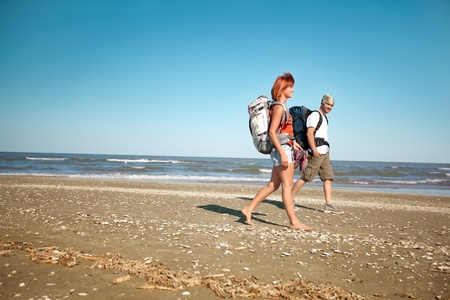 happy, young couple walking together on a deserted beach, wearing backpacks Stock Photo - 11532569
