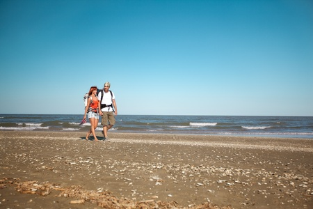 happy, young couple walking together on a deserted beach, wearing backpacks photo