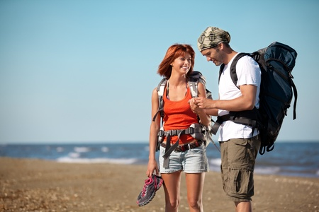happy, young couple walking together on a deserted beach, wearing backpacks, talking  photo