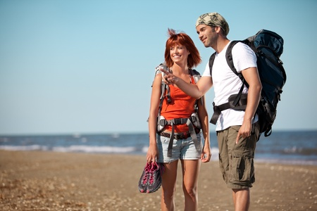 happy, young couple walking together on a deserted beach, wearing backpacks. the man points to a place next to them photo