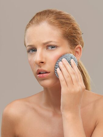 scrubber: closeup beauty portrait of beautiful funny blonde woman cleaning her skin with a metal dish scrubber