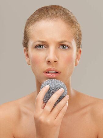 exfoliate: closeup beauty portrait of beautiful funny blonde woman cleaning her skin with a metal dish scrubber