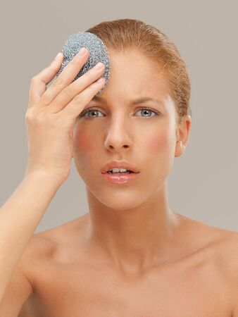 dry skin: closeup beauty portrait of beautiful funny blonde woman cleaning her skin with a metal dish scrubber