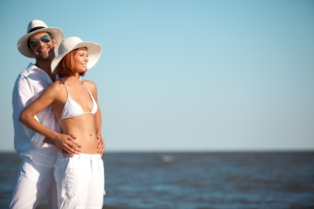 happy young couple, dressed in white, standing on a beach, smiling, holding each other photo