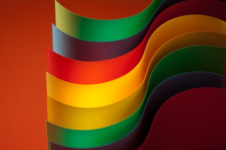 fan shaped: macro image of colorful curved sheets of paper shaped like a fan, on orange background Stock Photo