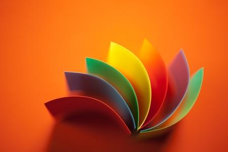 paper craft: imagen macro de coloridas l�minas curvadas de papel con forma de abanico, sobre fondo naranja