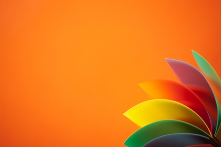 asymmetry: macro image of colorful curved sheets of paper shaped like a fan, on orange background Stock Photo