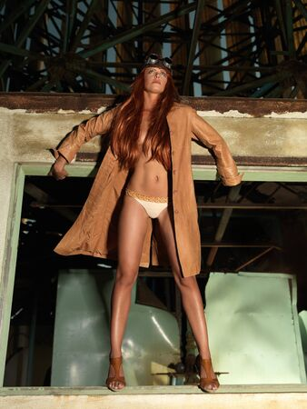 fashion portrait of beautiful, young woman, dressed in a vintage aviator outfit, standing in a window frame photo