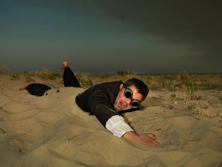 young, active businessman, dressed in a black suit, swimming through the sand on the sea shore; conceptual Stock Photo