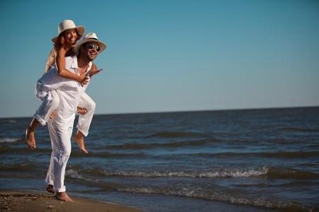is playful: joven pareja feliz vestida de blanco, en la playa, en un paseo el de lengüeta
