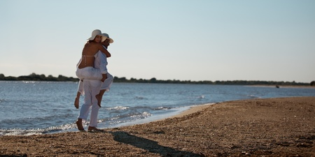 piggy back: happy young couple dressed in white, on the beach, on a piggy back ride