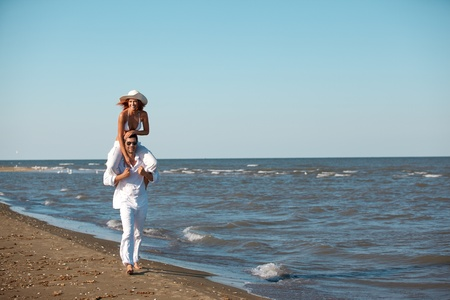 piggyback ride: happy young couple dressed in white, on the beach, on a piggy back ride