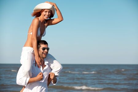 happy young couple dressed in white, on the beach, on a piggy back ride photo