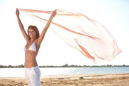 happy young woman running on a beach holding a silk scarf in her hands photo