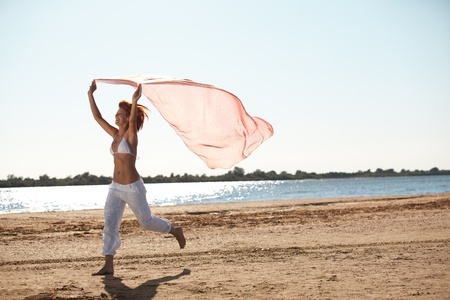 running pants: happy young woman running on a beach holding a silk scarf in her hands