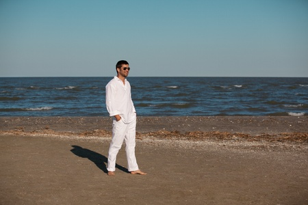 relaxed young man, dressed in white, taking a walk along the sea shore, in the summer photo