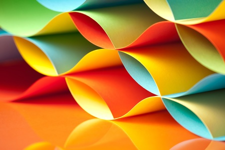 paper craft: background macro image of colorful origami pattern made of curved sheets of paper, with mirror reflexion