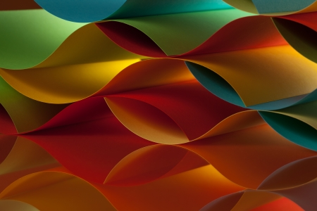 background macro image of colorful origami pattern made of curved sheets of paper, with mirror reflexion photo