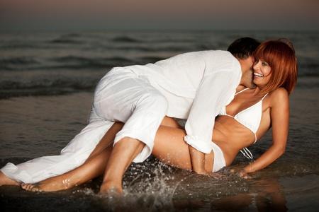 joven pareja feliz abrazando en una orilla de la playa del desierto. photo