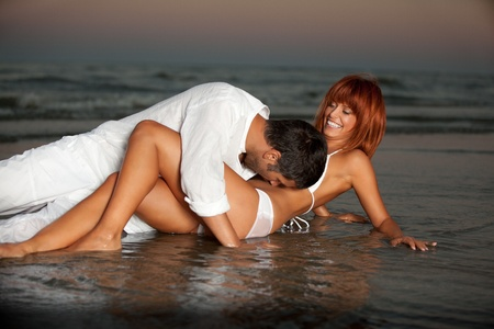 beach kiss: happy young couple hugging on a desert beach shore.