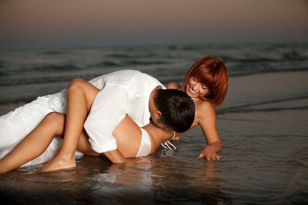 happy young couple hugging on a desert beach shore.