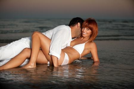 baiser amoureux: jeune couple heureux �treignant sur un rivage de plage d�sert.