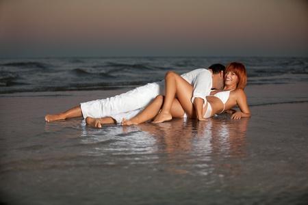 baiser amoureux: jeune couple heureux étreignant sur un rivage de plage désert.
