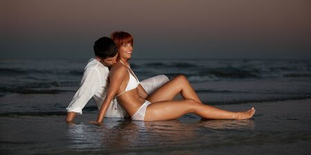 lovers kissing: happy young couple hugging on a desert beach shore.