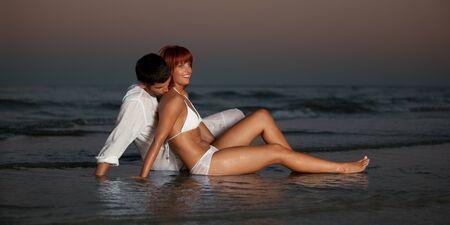 enamorados besandose: joven pareja feliz abrazando en una orilla de la playa del desierto.