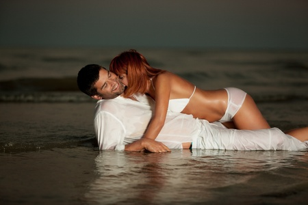 happy young couple hugging on a desert beach shore. photo