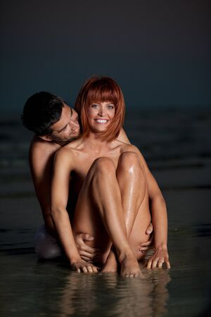 sexy, young couple playing holding each other on the beach, after sunset, smilling Stock Photo - 13040324