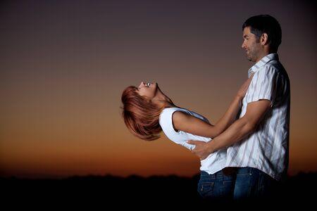 sexy, jeu jeune couple tenant les uns des autres sur la plage, apr�s le coucher du soleil, smilling photo