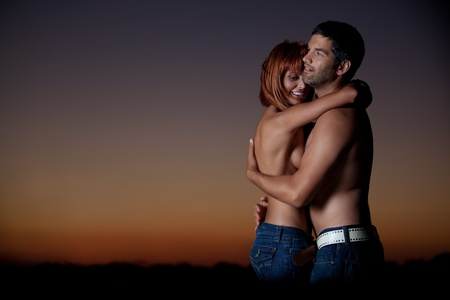 sexy, young couple playing holding each other on the beach, after sunset, smilling Stock Photo - 13040246