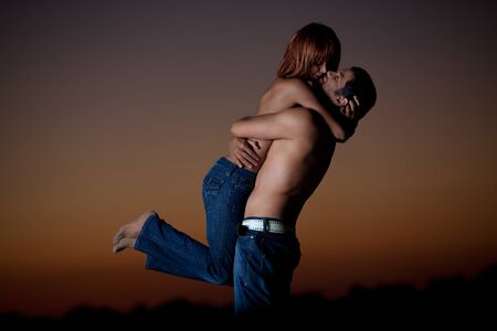 sexy, young couple playing holding each other on the beach, after sunset, smilling Stock Photo - 13040282