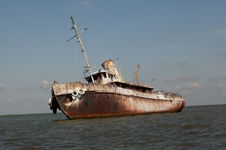 sea pollution: side view of abandoned wrecked ship in seaside landscape