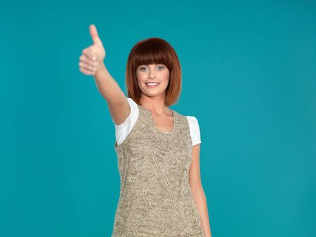 beautiful, young woman, smiling and showing her thumb up, on blue background photo