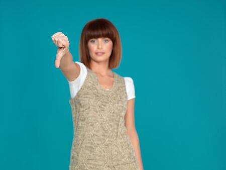 beautiful, young woman, showing her thumb down, on blue background Stock Photo - 13239383