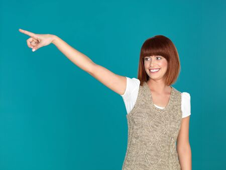 beautiful, young woman, smiling and pointing to the left, on blue background Stock Photo - 13239953