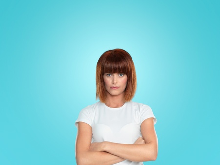 beautiful, young woman, with her arms crossed and a hostile face expression, on blue background Stock Photo - 13238105